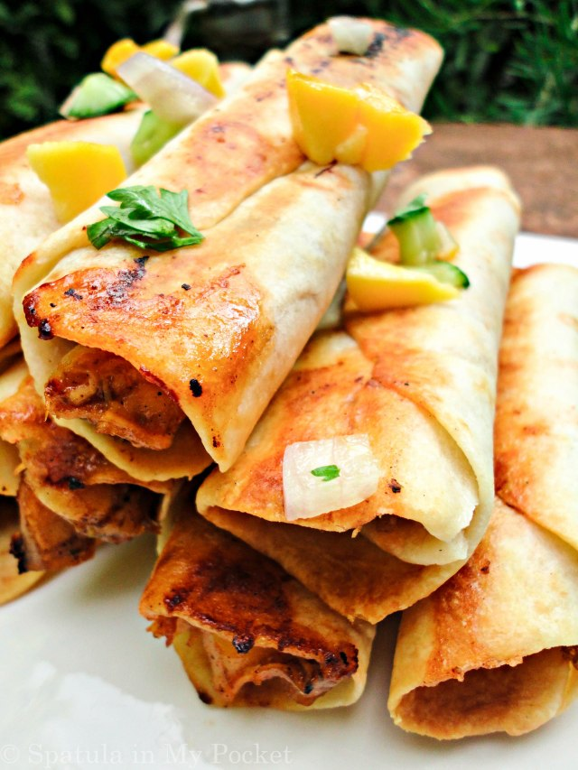 Hawaiian BBQ Taquitos. Filled with pineapples and mangoes, paired with a spicy tangy BBQ chicken, caramelized onions, and loads of fresh cheddar cheese.